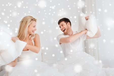 people, family, bedtime and fun concept - happy couple having pillow fight in bed at home over snow
