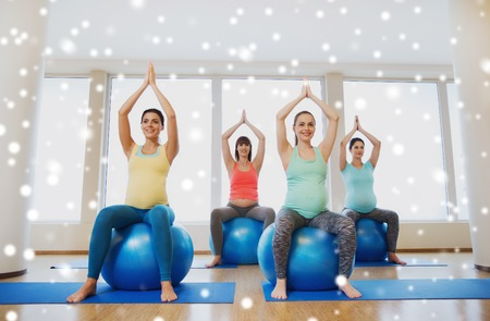 pregnancy, sport, fitness, people and healthy lifestyle concept - group of happy pregnant women exercising on stability balls in gym over snow Stock Photo