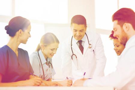 consulta médica: el hospital, la profesión, la gente y el concepto de la medicina - grupo de médicos felices reuniones y tomando notas en el consultorio médico Foto de archivo