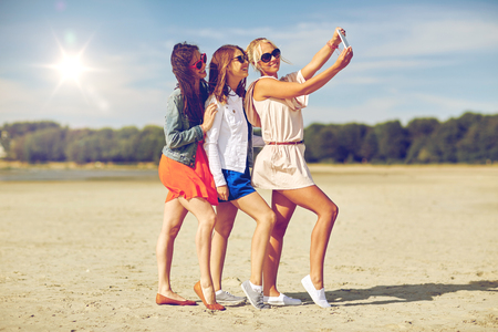 young group: summer vacation, holidays, travel, technology and people concept- group of smiling young women taking selfie with smartphone on beach Stock Photo