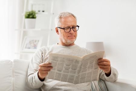 레저, 정보, 사람들 및 미디어 개념 - 집에서 신문을 읽는 안경에 수석 남자 스톡 콘텐츠