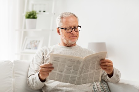 leisure, information, people and mass media concept - senior man in glasses reading newspaper at home Banque d'images