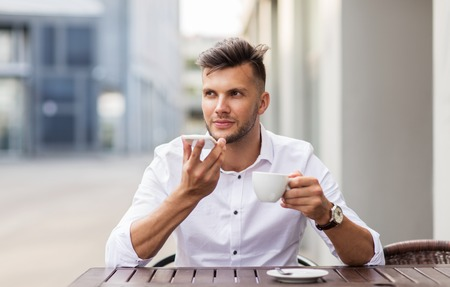 using voice: business, technology, communication and people concept - young man with coffee using voice command recorder on smartphone at city street cafe