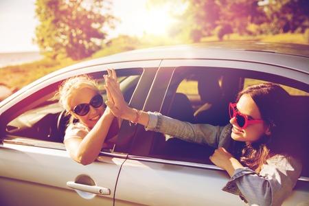 persona feliz: vacaciones de verano, vacaciones, viaje, viaje por carretera y el concepto de la gente - adolescentes felices o mujeres jóvenes en un coche junto al mar en la fabricación de alta cinco gesto