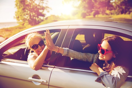 summer vacation, holidays, travel, road trip and people concept - happy teenage girls or young women in car at seaside making high five gesture Foto de archivo