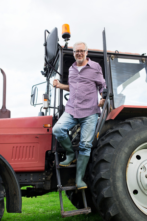 getting out: farming, agriculture and people concept - senior man or farmer getting out of tractor at farm