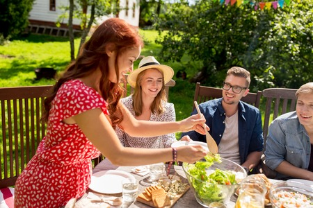 garden barbecue: leisure, holidays, eating, people and food concept - happy friends having dinner at summer garden party