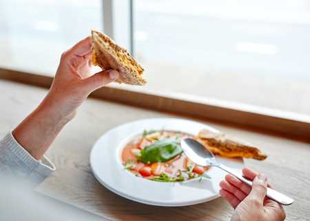 gazpacho: food, dinner, culinary and people concept - woman eating gazpacho soup with sandwich and spoon at restaurant