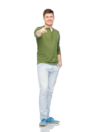 gesture, choice and people concept - happy smiling young man pointing finger to you over white