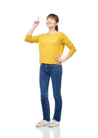 pointing finger up: people, ethnicity and idea concept - happy asian young woman pointing finger up over white