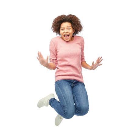 people in action: people, motion and action concept - happy african american young woman jumping over white Stock Photo