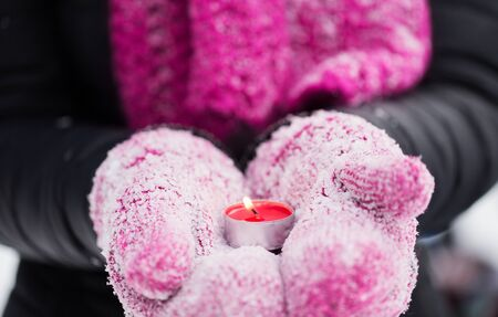 winter holidays, christmas and people concept - close up of hands in mittens holding burning tea candle outdoors