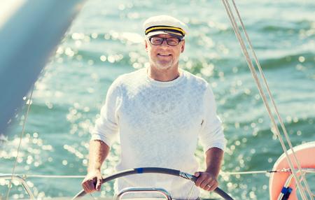 Segeln, Alter, Tourismus, Reisen und Menschen Konzept - glücklich älterer Mann im Kapitän-Hut auf Lenkrad und Segelboot oder Yacht in Meer schwimmen Navigation