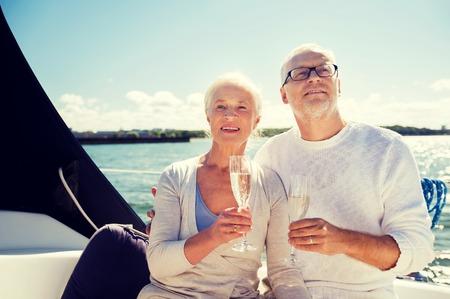 항해, 나이, 여행, 휴일 및 사람들이 개념 - 항해 보트 나 요트 갑판 바다에 떠있는 샴페인 안경 행복 수석 부부