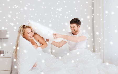 people, family, bedtime and fun concept - happy couple having pillow fight in bed at home over snow Stock Photo