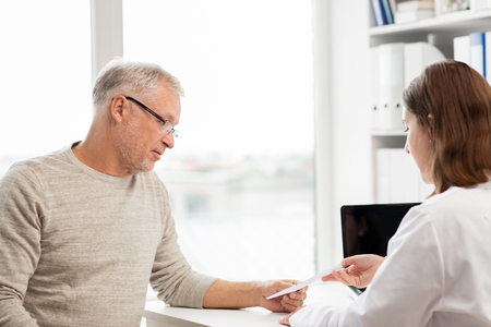 medicine, age, health care and people concept - senior man and doctor with prescription meeting in medical office at hospital Stock Photo