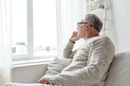 vecchiaia: vecchiaia, problema e le persone concetto - l'uomo anziano in bicchieri pensare e di guardare attraverso la finestra in casa