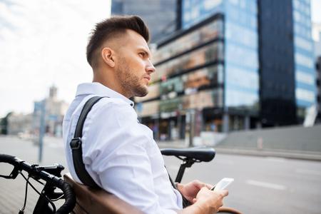 personas pensando: las personas, la tecnología, la comunicación y el estilo de vida - hombre joven y sonriente feliz con la bicicleta y se sienta en el banco de la ciudad