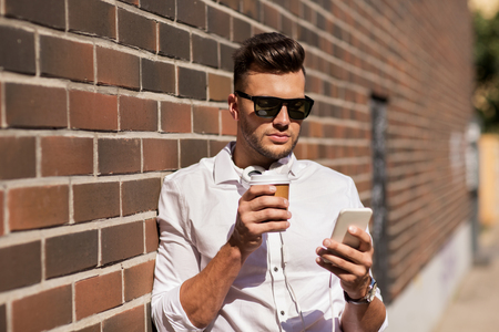 technology and people concept - young man in sunglasses with smartphone and coffee cup on city street Stock Photo
