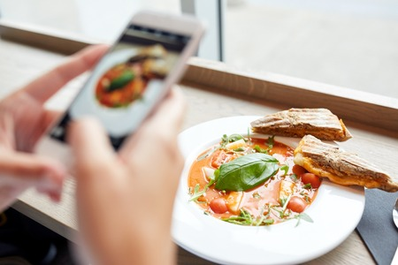 tomando refresco: alimentos, alimentación, tecnología culinaria y el concepto de personas - manos de la mujer con la foto gazpacho sopa de pantalla del teléfono inteligente en el restaurante