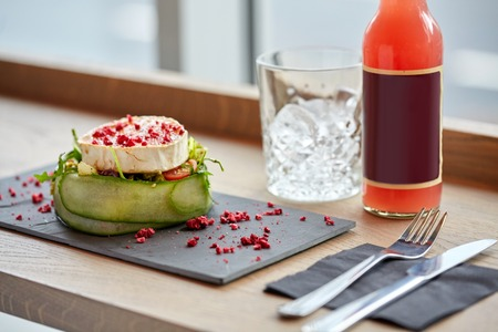 goat cheese: food, eating and object concept - goat cheese salad with vegetables, bottle of drink, glass with ice and cutlery at restaurant or cafe