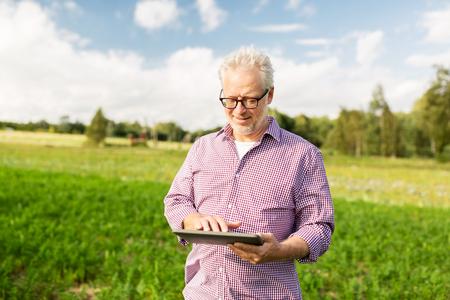agricultura: la agricultura, la agricultura, la tecnología, la vejez y las personas concepto - hombre mayor feliz con el ordenador de la PC de la tableta en el condado o de la granja Foto de archivo