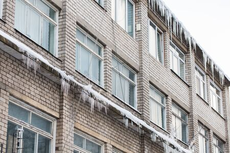 overhang: season, housing and winter concept - icicles on building or living house facade