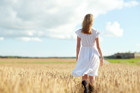summer dress: happiness, nature, summer holidays, vacation and people concept - young woman in white dress walking along cereal field
