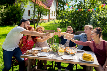 home and garden: summer, holidays, celebration people and food concept - happy friends having garden party and clinking glasses