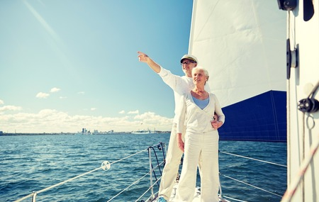 sailing, age, tourism, travel and people concept - happy senior couple pointing finger to something on sail boat or yacht deck floating in sea