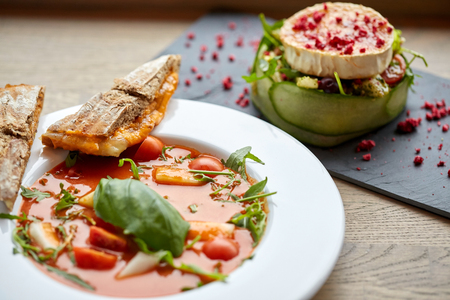 gaspacho: food, culinary, haute cuisine and cooking concept - goat cheese salad with vegetables and dried raspberries and plate of gazpacho soup at restaurant or cafe Stock Photo