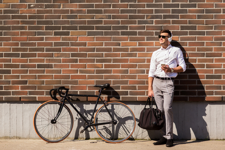 metrosexual: people, technology and lifestyle - happy young man with headphones, smartphone and bicycle listening to music in city
