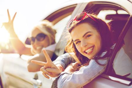 persona feliz: vacaciones de verano, vacaciones, viaje, viaje por carretera y el concepto de la gente - adolescentes felices o mujeres jóvenes en un coche junto al mar en