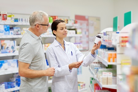 pharmaceutics: medicine, pharmaceutics, health care and people concept - happy pharmacist and senior man customer with drug and prescription at drugstore