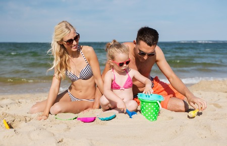 family playing: family, travel, vacation and people concept - happy man, woman and little girl in sunglasses playing with sand toys on summer beach