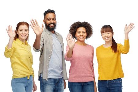 多様性、競争、民族性および人々 のコンセプト - 幸せな笑みを浮かべて男性と白で手を振る女性の国際的なグループ