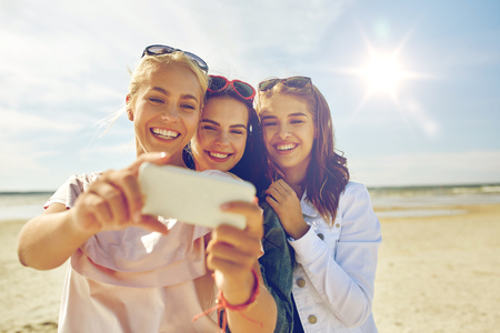 sulfide: summer vacation, holidays, travel, technology and people concept- group of smiling young women taking sulfide with smartphone on beach