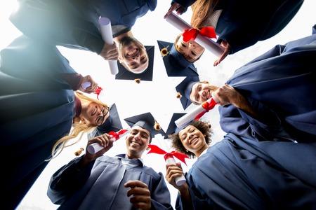 la educación, la graduación y el concepto de personas - grupo de estudiantes internacionales felices en juntas de mortero y vestidos de licenciatura de pie en círculo con diplomas