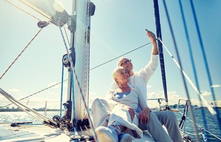 vela, tecnologia, turismo, viaggi e persone Concetto - felice coppia senior con lo smartphone di prendere selfie in barca a vela o del ponte yacht galleggianti in mare