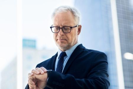 puntualidad: negocio, la puntualidad y el concepto de la gente - hombre de negocios mayor que controla el tiempo en el reloj de pulsera o reloj inteligente en su mano en la ciudad