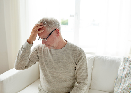 megrim: healthcare, pain, stress, age and people concept - senior man suffering from headache at home Stock Photo