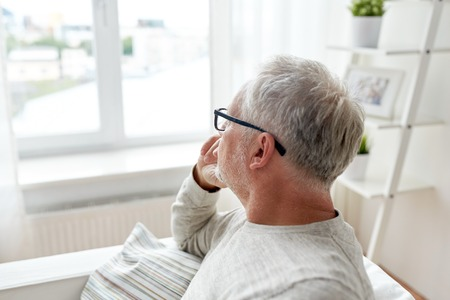 unhappy man: old age, problem and people concept - senior man in glasses thinking and looking through window at home