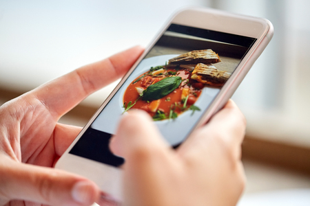 gaspacho: food, eating, technology, culinary and people concept - woman hands with gazpacho soup photo on smartphone screen at restaurant