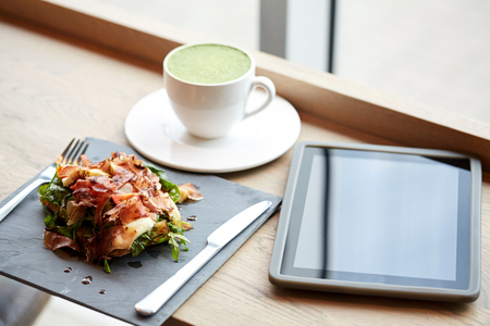 food, dinner, haute cuisine and eating concept - prosciutto ham salad on stone plate with matcha green tea latte and tablet pc computer at restaurant Stock Photo