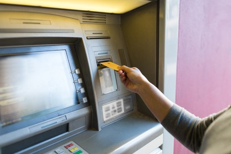 inserting: finance, money, bank and people concept - close up of woman hand inserting card to atm machine