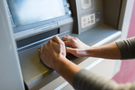 pin code: finance, money, bank and people concept - close up of hand entering pin code at atm machine