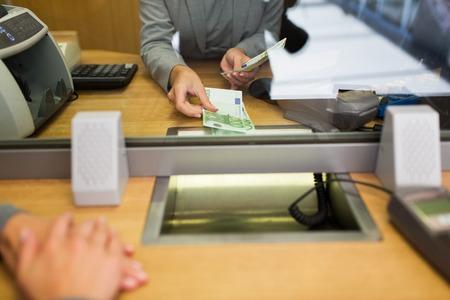 Mensen, terugtrekking, spaar- en financieringsconcept - clerk die geld aan klanten op bankkantoor of valuta-wisselaar geeft Stockfoto