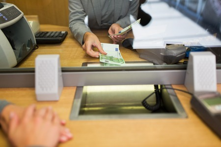 exchanger: people, withdrawal, saving and finance concept - clerk giving cash money to customer at bank office or currency exchanger