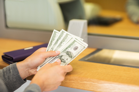 exchanger: people, withdrawal, saving and finance concept - hands with cash money at bank office or currency exchanger