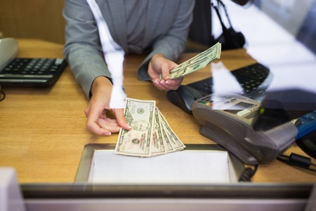 Mensen, terugtrekking, spaar- en financieringsconcept - clerk die geld aan klanten op bankkantoor of valuta-wisselaar geeft Stockfoto - 67412208